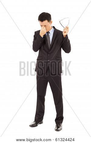 Young Businessman Rubbing His Eyes And Holding Glasses