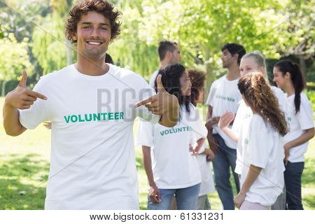 Portrait of male volunteer pointing at tshirt with friends in background