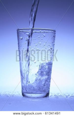 Glass with clear liquid being poured with blue hue