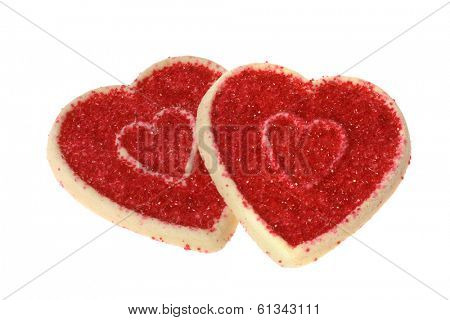 two heart shaped sugar cookies with red sprinkles on white