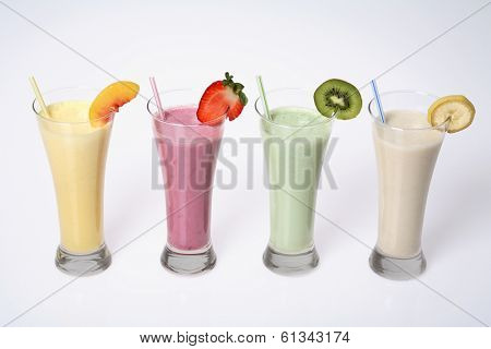still life of four milkshakes or smoothies in tall glasses