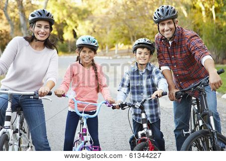 Portrait Of Hispanic Family On Cycle Ride In Countryside