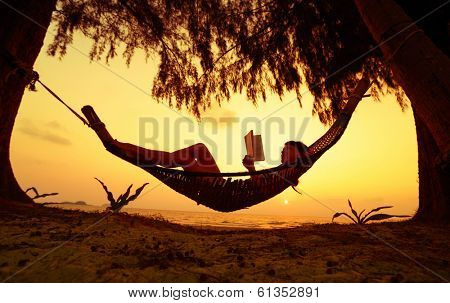 Young lady reading the book in the hammock on tropical beach at sunset