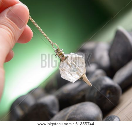 Hand with pendulum, tool for dowsing.