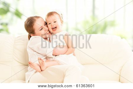 Happy Family. Mother And Baby Daughter Plays  On The Sofa