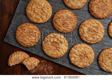 Freshly baked snickerdoodle cookies on slate serving tray as seen from above.  Rustic still life with directional, natural lighting for effect.