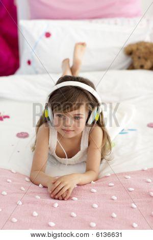 Smiling little girl listening music in bed