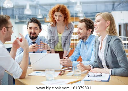 Group of business partners listening to their colleague explanations at meeting