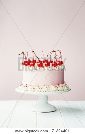 Cake decorated with frosting and maraschino cherries