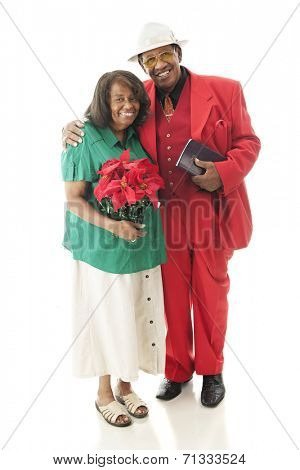 Full-length image of a senior couple dressed for Christmas.  On a white background.