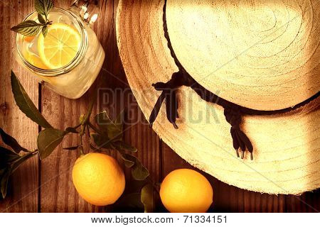 Fresh Squeezed Lemonade on a rustic wooden table with lemons and a sun hat. Horizontal format with an instagram feel, shot from a high angle, with vignette.