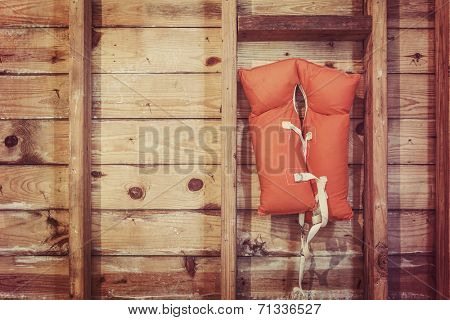 Old orange life jacket hanging in a boat house