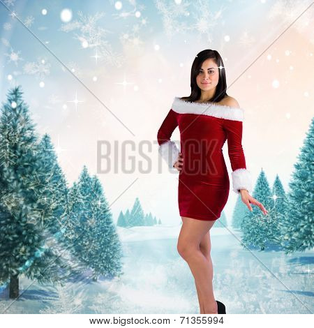 Pretty girl smiling in santa outfit against snowy landscape with fir trees poster