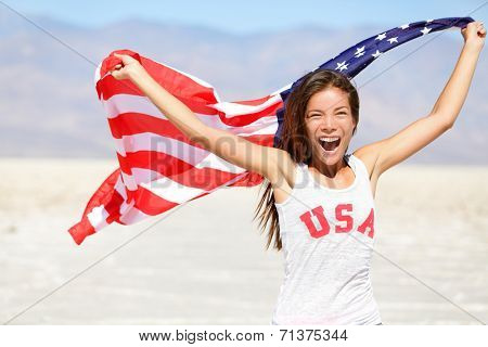 American flag - woman USA sport athlete winner cheering waving US flag Stars and Stripes outdoor running in nature. Beautiful cheering happy young multicultural girl joyful and excited.
