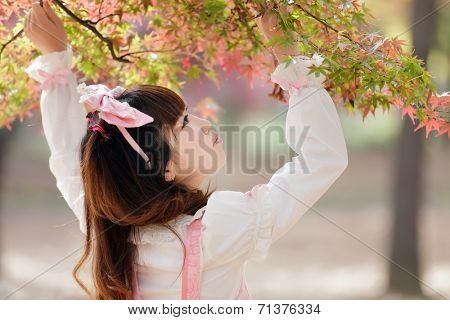 Japanese girl in lolita cosplay fashion looking autumn leaves in a Tokyo park