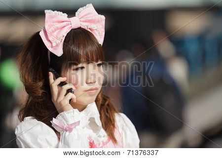 Japanese lolita cosplay woman using her mobile phone in a Tokyo street,, Japan