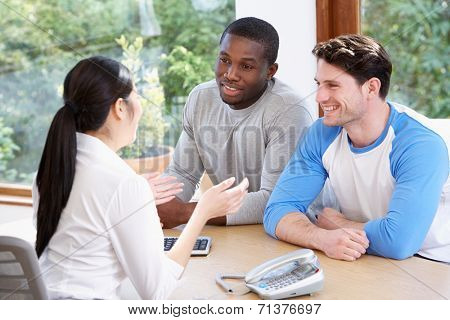 Male Couple Talking With Financial Advisor In Office