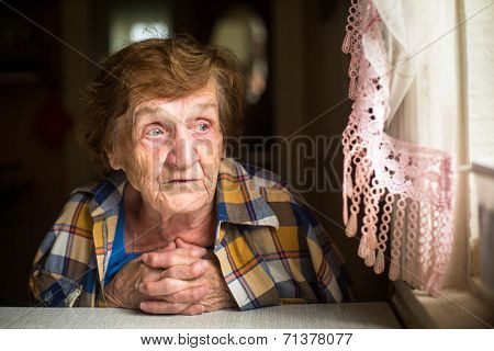 Old lonely woman sitting at a table near the window in his house. Old age. Loneliness.