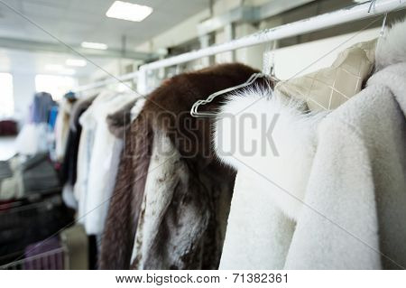 Clean clothes hanging on hangers at dry cleaner's