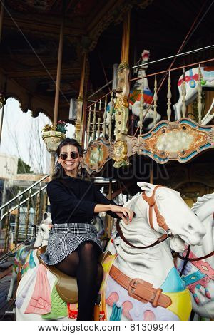 Young attractive woman enjoying time while riding on a merry go round on holidays