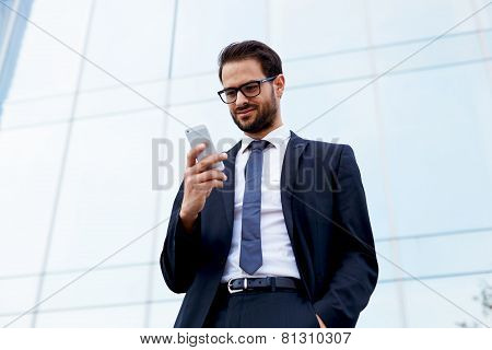 Happy businessman smiling as he reads a text message standing outside the office