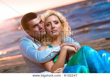 Young couple in love near the sea at sunset