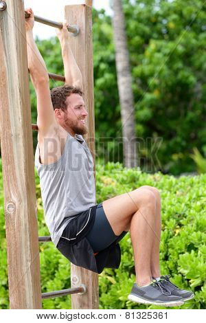 Abs exercise outside fitness station park. Man training core muscles with leg lift on vertical ladder rack on an outdoors gym center.