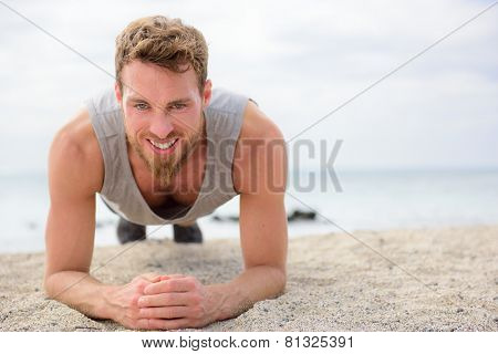 training fitness man doing plank core exercise working out his midsection muscles. Fit athlete fitness training planking exercising outside in summer on beach.