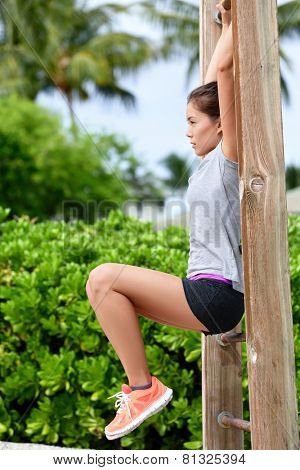 Fitness woman workout doing abs exercises on outdoor beach gym. Asian girl training abs by raising legs on a vertical bars rack during a fitness station circuit routine.