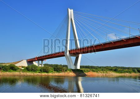 A Big Red And White Bridge Through The River