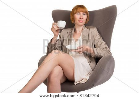Young lady in office style sitting on modern chair with a cup of coffee