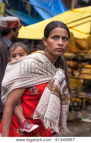 Wom?n in traditional clothing carrying a child in Manali old Market .