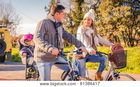 Family with little daughter riding bicycles in the nature