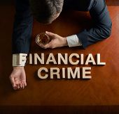 Phrase Financial Crime made of wooden block letters and devastated middle aged caucasian man in a black suit sitting at the table with the glass of whiskey, top view composition with dramatic lighting poster