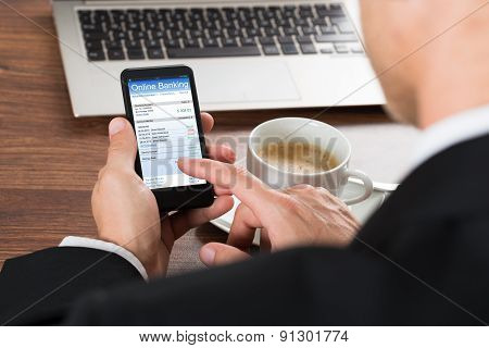Businessman Using Online Banking Service On Cellphone