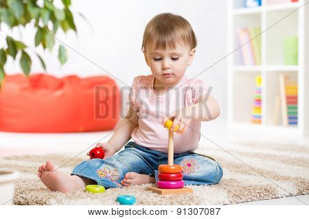 Adorable toddler girl playing in nursery room