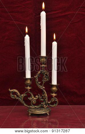 Antique Candelabra With Three Melting Candles On A Dark Red Velvet Background