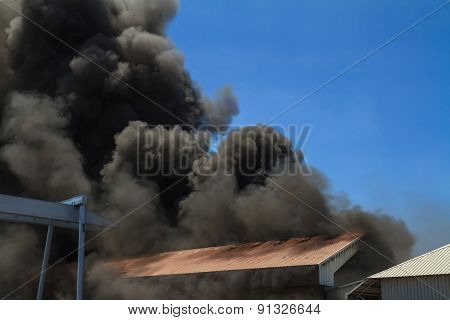 Burning warehouses with black smoke against blue sky