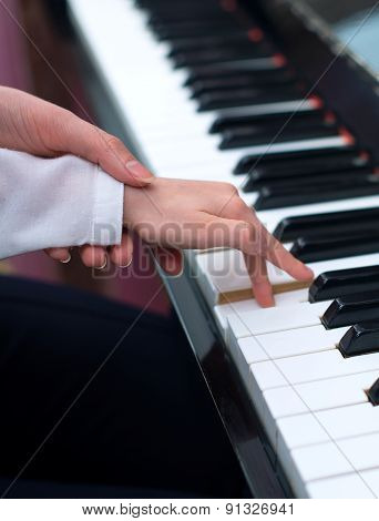 Woman teaching little girl to play the piano. poster