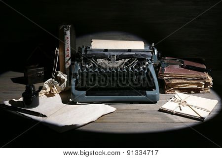 Retro typewriter in lamplight on wooden background