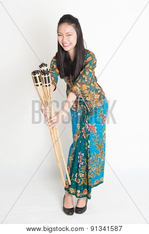 Full body portrait of Southeast Asian woman in batik dress hands holding pelita standing on plain background.