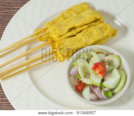 Grilled Pork Satay With Cucumber Salad On A Plate