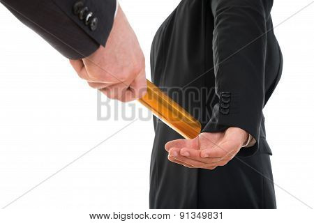 Person Passing A Golden Relay Baton To Another Person