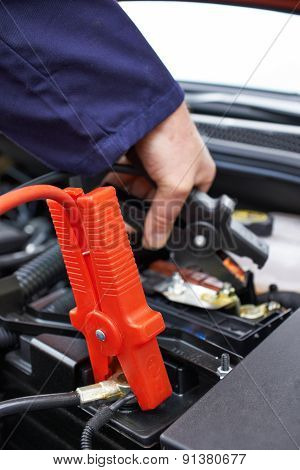 Close-Up Of Mechanic Attaching Jumper Cables To Car Battery poster