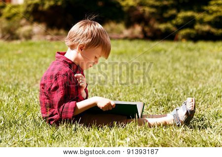 Profile of little boy reading book
