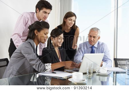 Group Of Business People Having Meeting Around Laptop At Glass Table