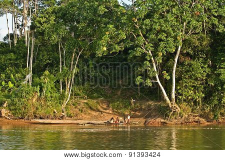 Unidentified local indigenous people next to Napo river in the rainforest, Yasuni National Park, Ecu