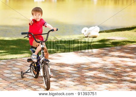 Little boy riding bike and giving thumbs up