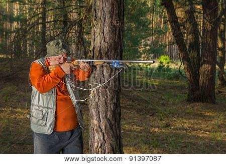 Senior hunter aim a rifle in forest poster