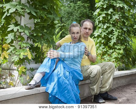 Young happy couple sits in the arbour twined greens